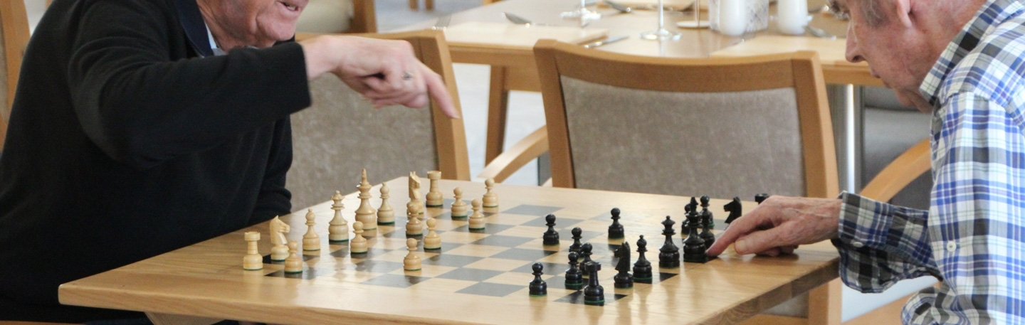 Residents play chess in the cafe